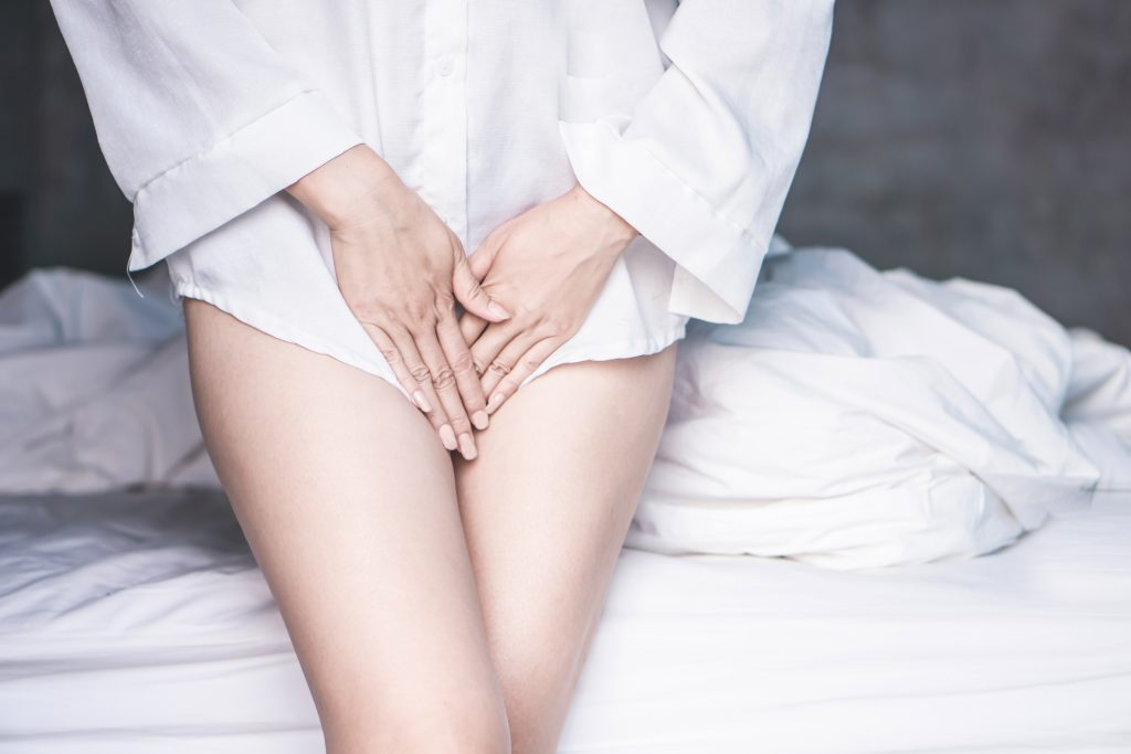 Period cramps, woman covering crotch area